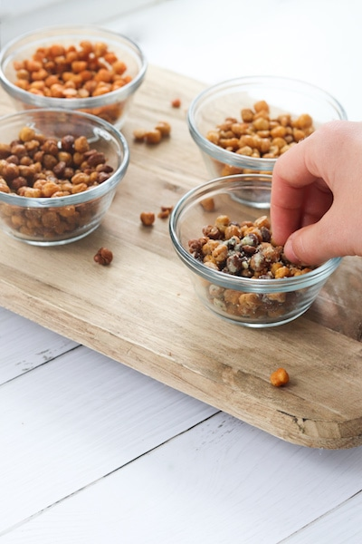 Roasted chickpeas seasoned 4 ways is a great snack under 100 calories a serving and provides about 4 grams of fiber and protein in a serving! They are easy to prepare and can be used in soups, salads, pasta or rice dishes or eaten straight from the oven. | mealswithmaggie.com #5ingredientsorless #roastedchickpeas #crunchy #easymealprep #easysnackidea #lowcaloriesnack #highproteinsnack #highfibersnack