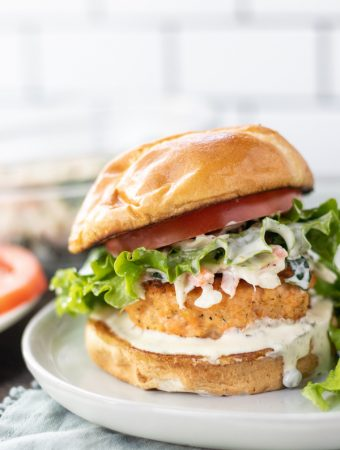 a salmon burger with a bun and lettuce on a plate.