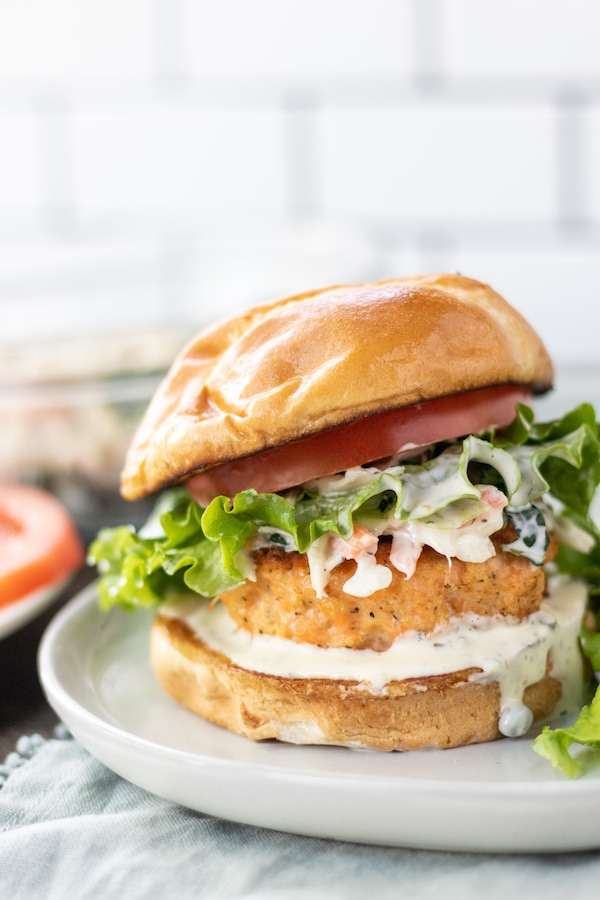 A salmon patty on a burger with a bun and lettuce on top.