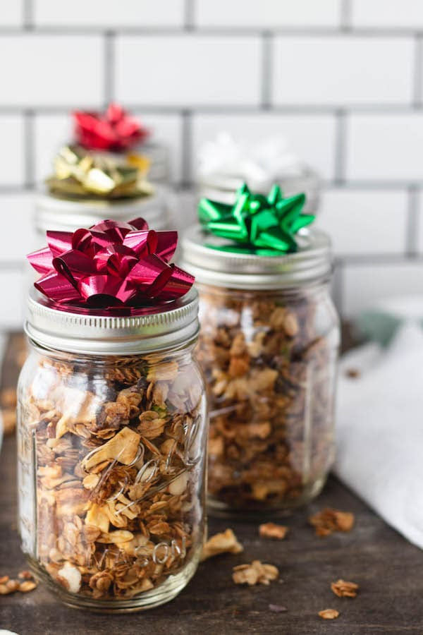 Mason jars filled with granola and a bow on top.