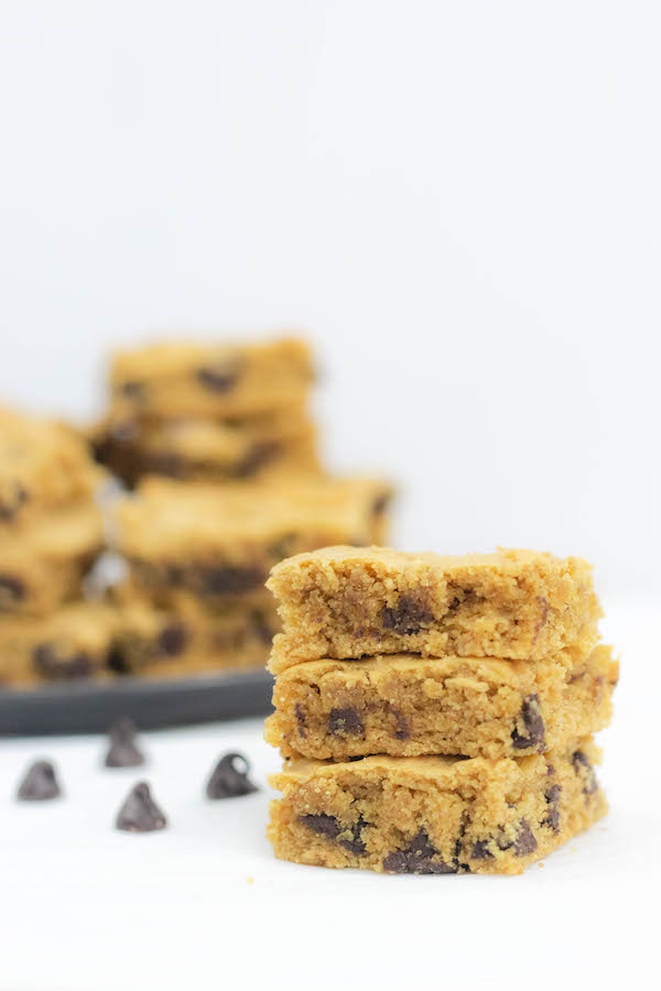 Healthy Peanut Butter Brownies stacked on a plate with chocolate chips