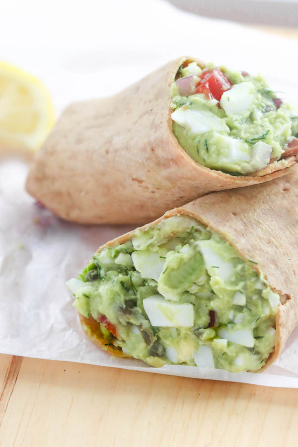 Avocado egg salad on a counter in a multi-grain wrap.