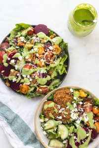 two salads in bowls with green goddess dressing drizzle