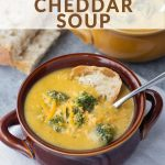 Broccoli cheddar soup in a bowl with bread and text above it.