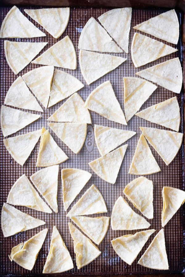 corn tortillas lined on a sheet pan