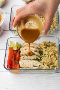 thai peanut sauce being poured on thia chicken meal prep bowl