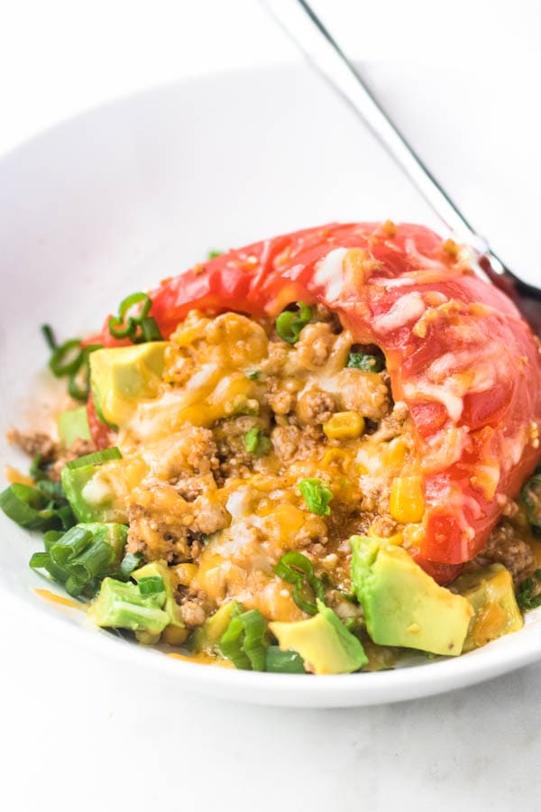 Stuffed pepper in a bowl with scallions and avocado on top.