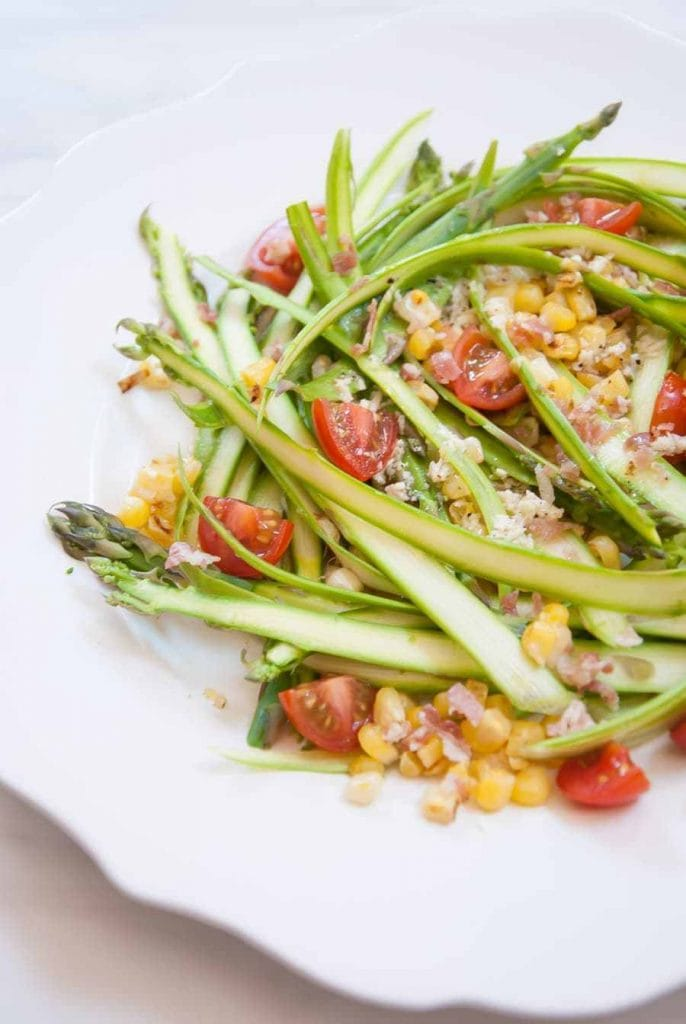 shaved asparagus with tomatoes and corn in it.