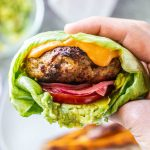 A hand holding a turkey burger in a lettuce wrap.