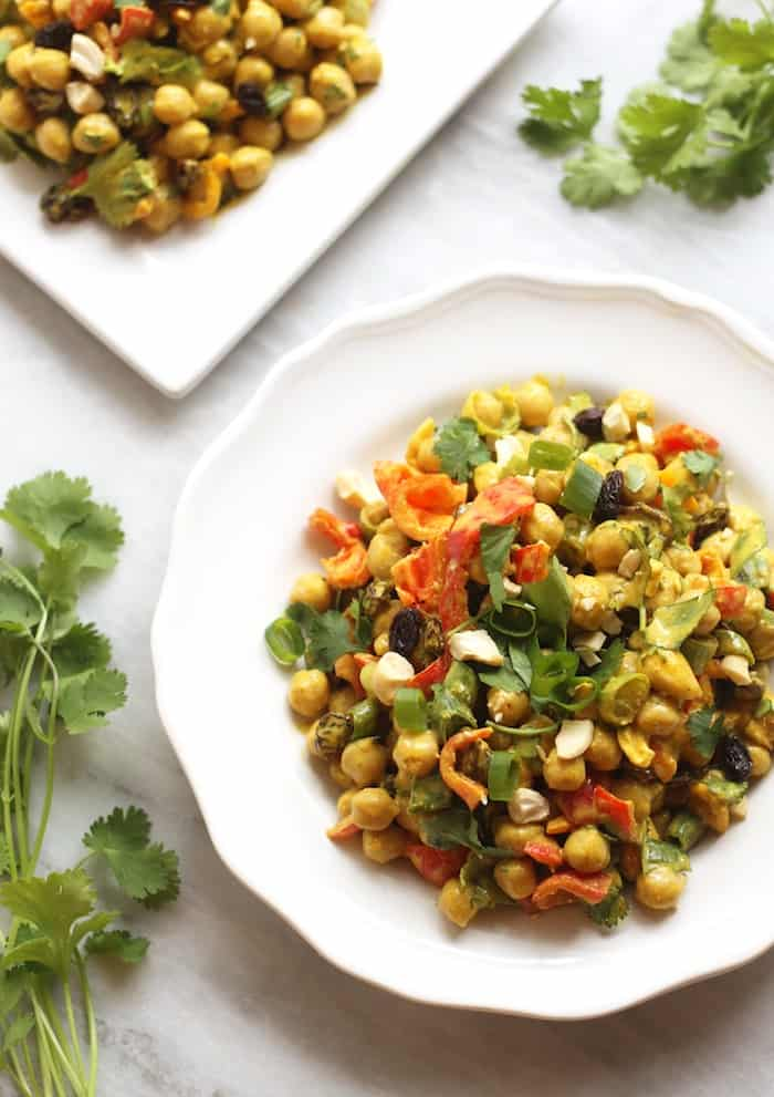 chickpea salad on a plate with cashews and green onions.