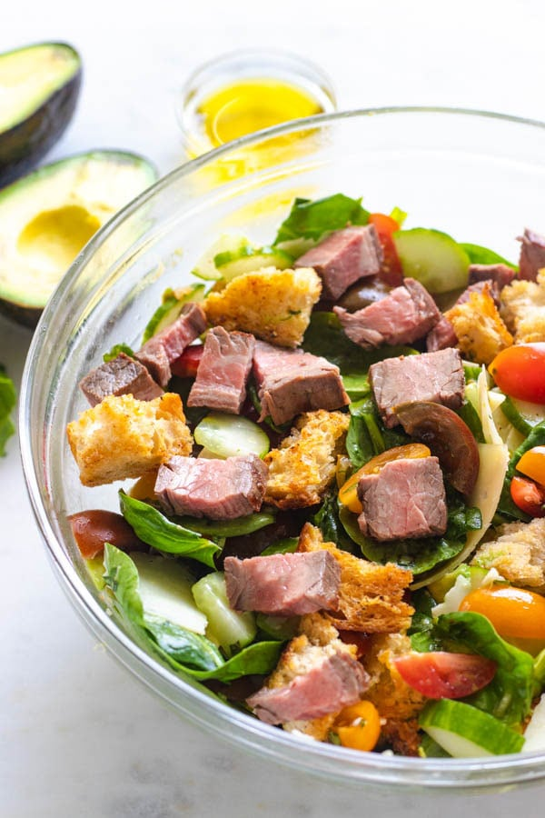Up close side view of steak salad in a bowl with croutons