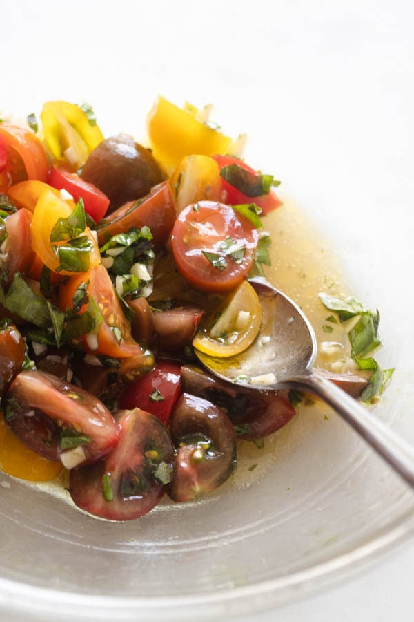 tomatoes in a bowl with a spoon and oil