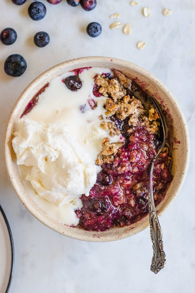 Blueberry crisp in a bowl with ice cream and a spoon.