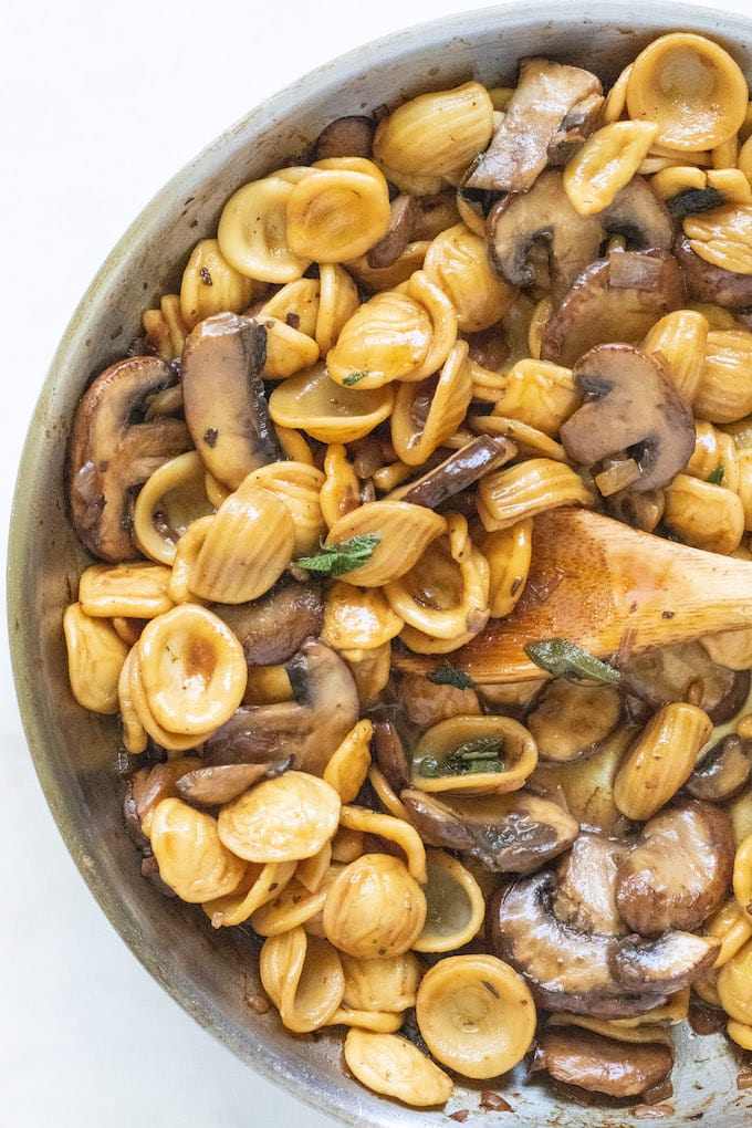 Pasta in a pan with mushrooms and sage.