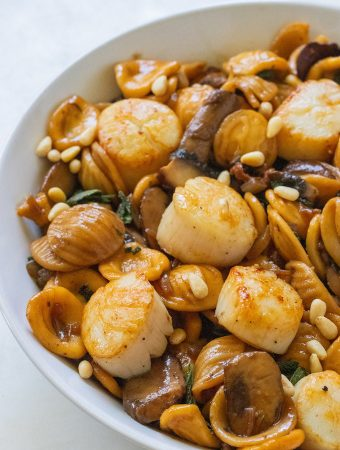 A side view of scallops with pine nuts sprinkled on top.