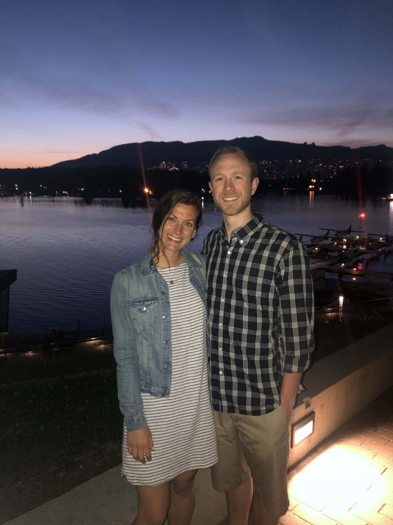 2 people standing on a dock in Vancouver at night with mountains in the background.