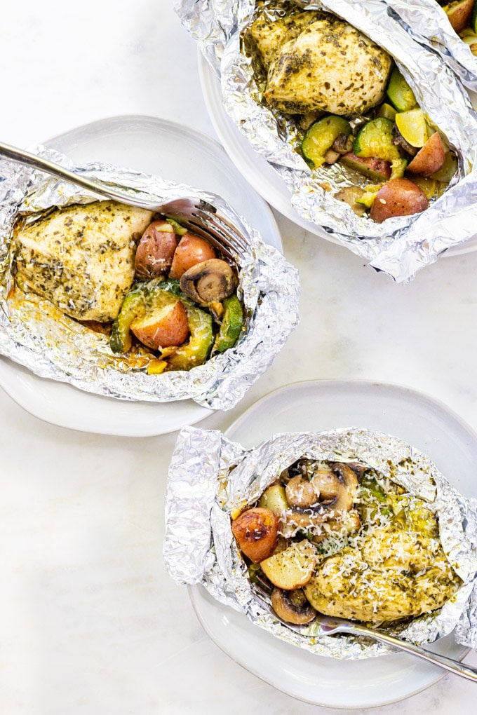 chicken and vegetables in foil packets with a fork