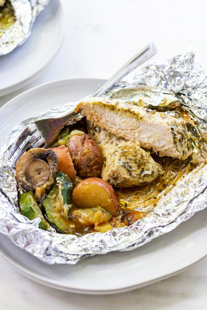 Cut chicken with vegetables in foil with a fork on a plate.