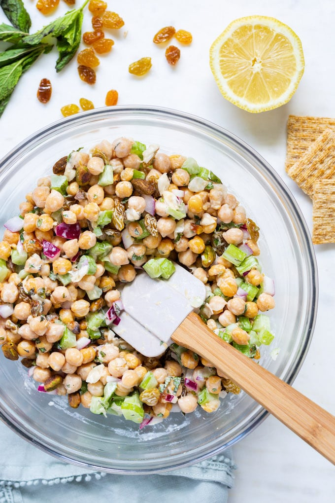 Chickpea salad with a spatula coming out of it with ingredients around it.