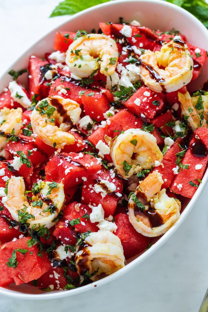 shrimp, feta and watermelon in a bowl with balsamic drizzled over it.