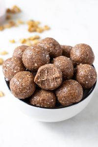 A bowl of protein balls with bite mark in one.