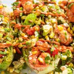 up close view of shrimp, corn and tomatoes on grilled romaine.