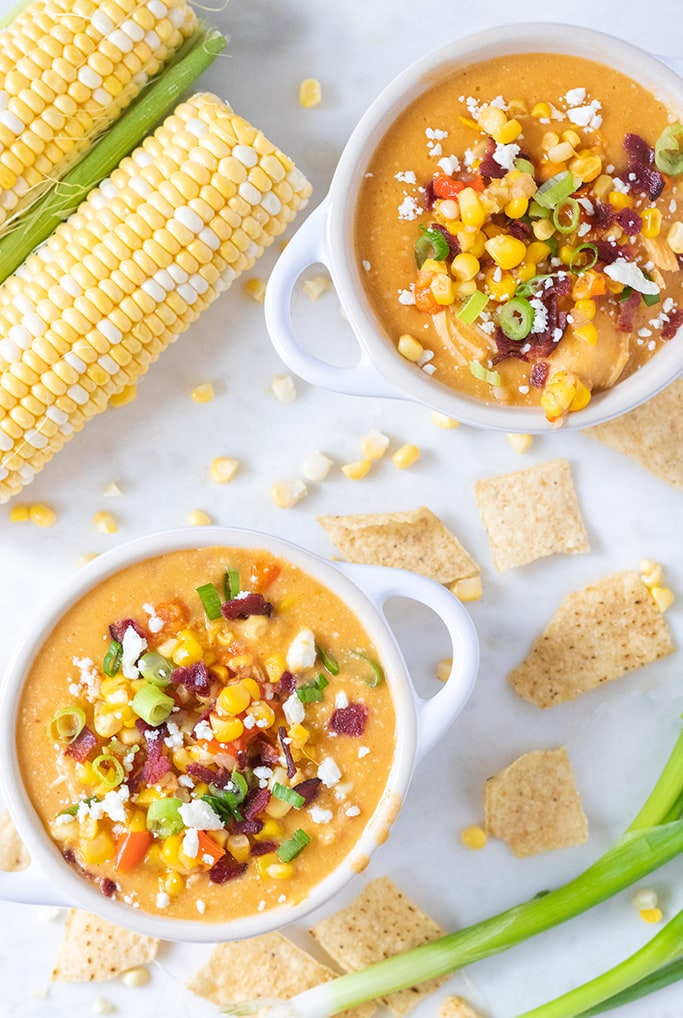 Overhead view of corn chowder with toppings