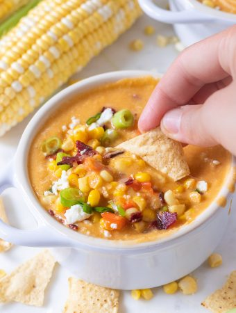 A chip being dunked in a bowl of corn chowder.