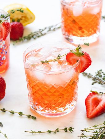 strawberry cocktail with vodka and thyme around it.