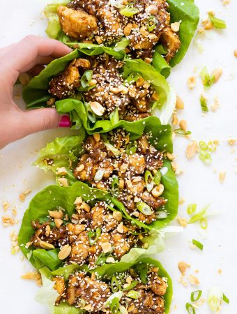 Hand grabbing a lettuce cup full of sesame ginger chicken