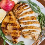 Apple cider chicken on plate with fresh herbs.