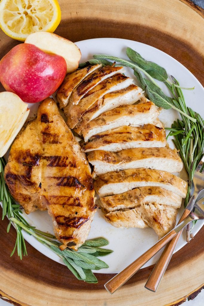 Apple Cider chicken on a plate with herbs and forks.