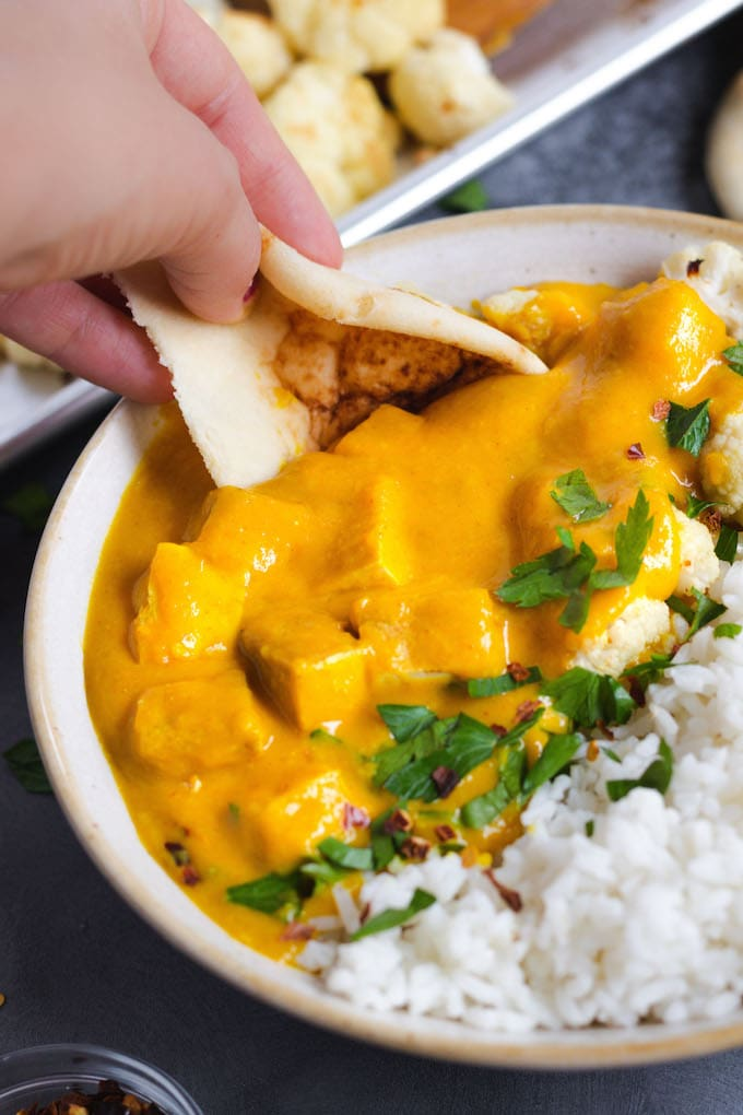 A hand dipping naan into butternut squash cauliflower curry.
