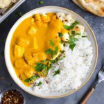 A bowl of butternut squash curry with toppings around it.