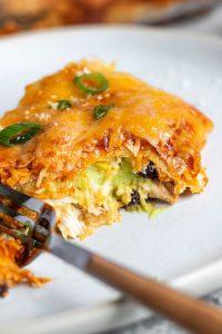 A piece of enchilada lasagna stuffed with avocado cream