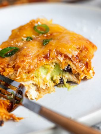 A piece of enchilada lasagna stuffed with avocado cream