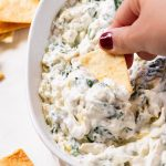 A chip dipped into a large bowl with spinach and artichoke dip.