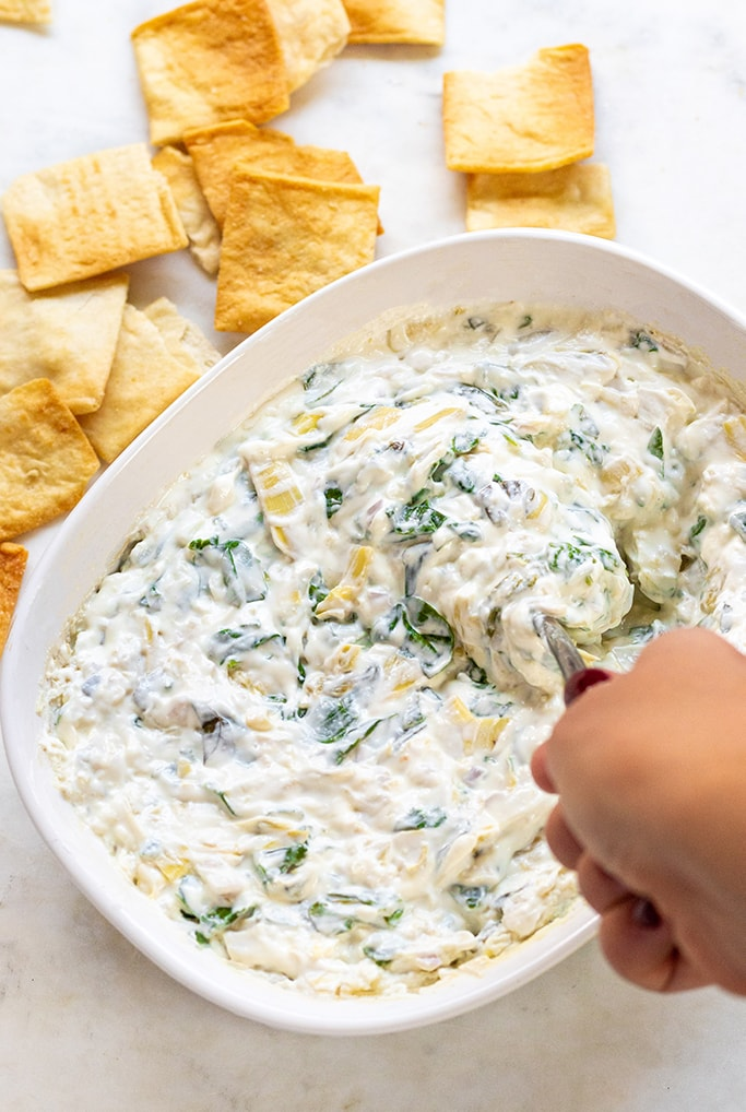 A bowl of spinach artichoke dip being stirred with a spoon.
