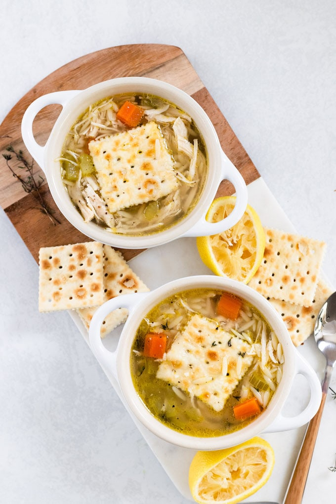 A bowl of soup with saltines and chicken and orzo soup.