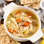 a bowl of lemon chicken orzo soup with crackers around it.