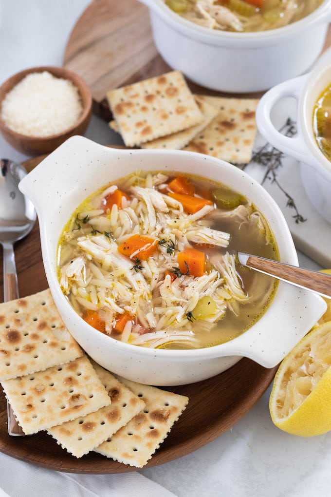 a bowl of soup with lemon, orzo, chicken and saltine crackers.