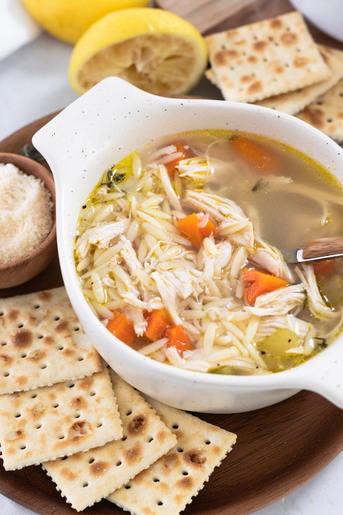 a bowl of soup with crackers and a spoon.