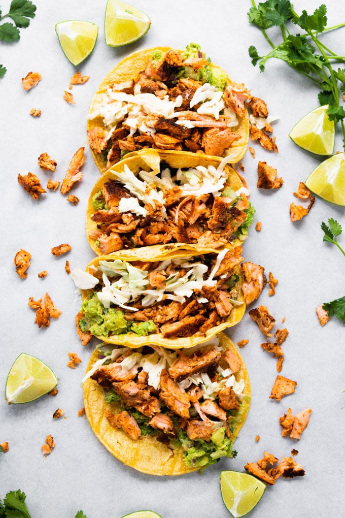 Tortillas lined up stuffed with blackened salmon and limes around it.