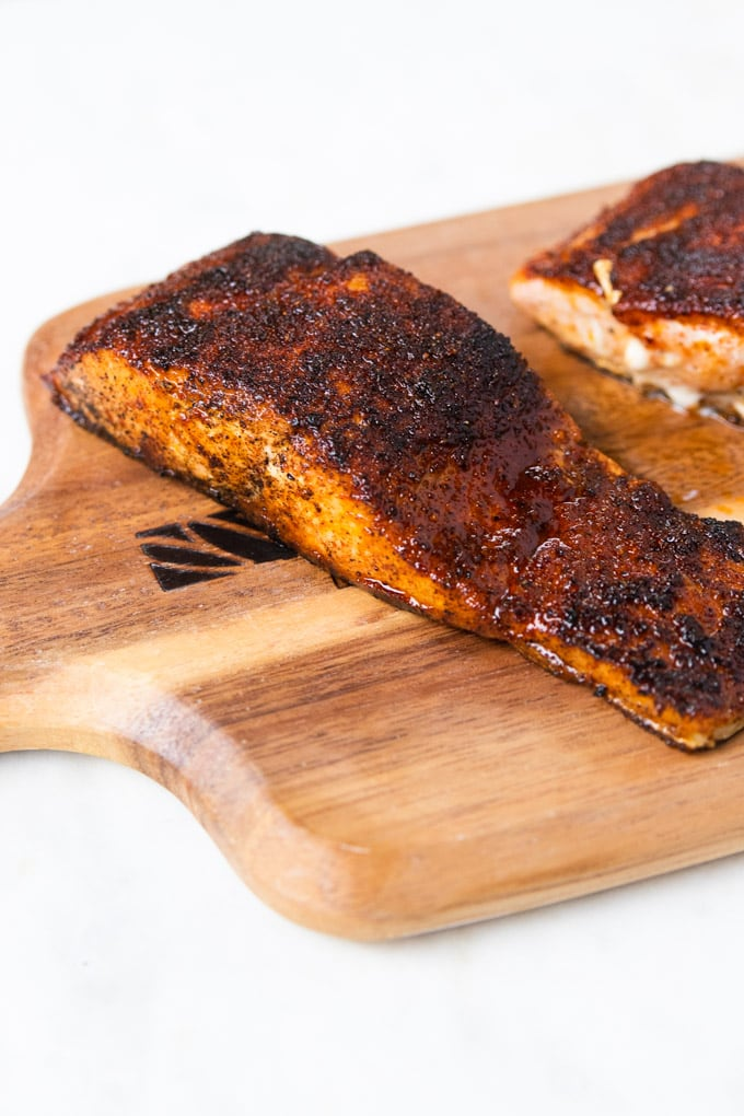 Salmon on a plank with blackened seasoning.