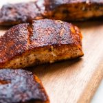 Blackened salmon filets on a wooden plank.