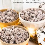 Popcorn puppy chow with halloween festive items around it.
