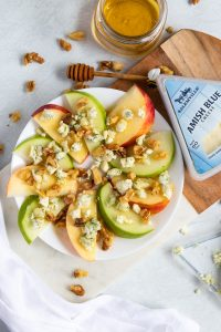 Blue cheese apples on a plate with cheese next to it.