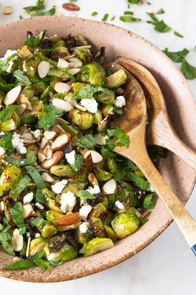 Spoons in a bowl with brussel sprout recipe.