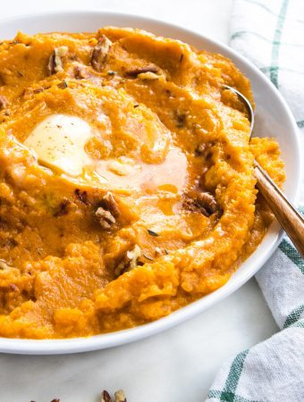 sweet potatoes in a bowl with butter and a spoon with pecans.