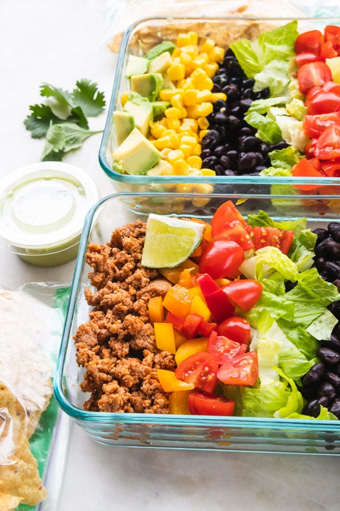 A side view of taco salad meal prep bowls with toppings on the side.
